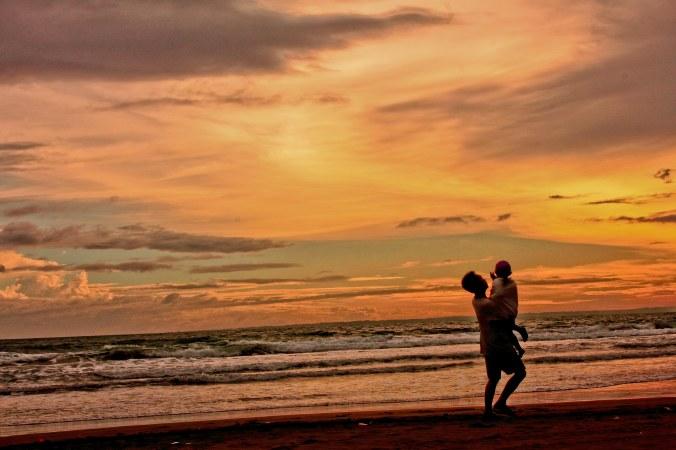 Seorang ayah, sedang mengajarkan kepada anaknya, untuk mencintai senja dan keindahan semesta.