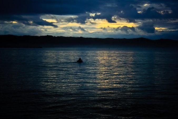 Awannya sedang egois, tetapi nelayan ban tetap mengayuh bannya menggunakan piring plastik ke tengah laut untuk menyerbar jala.