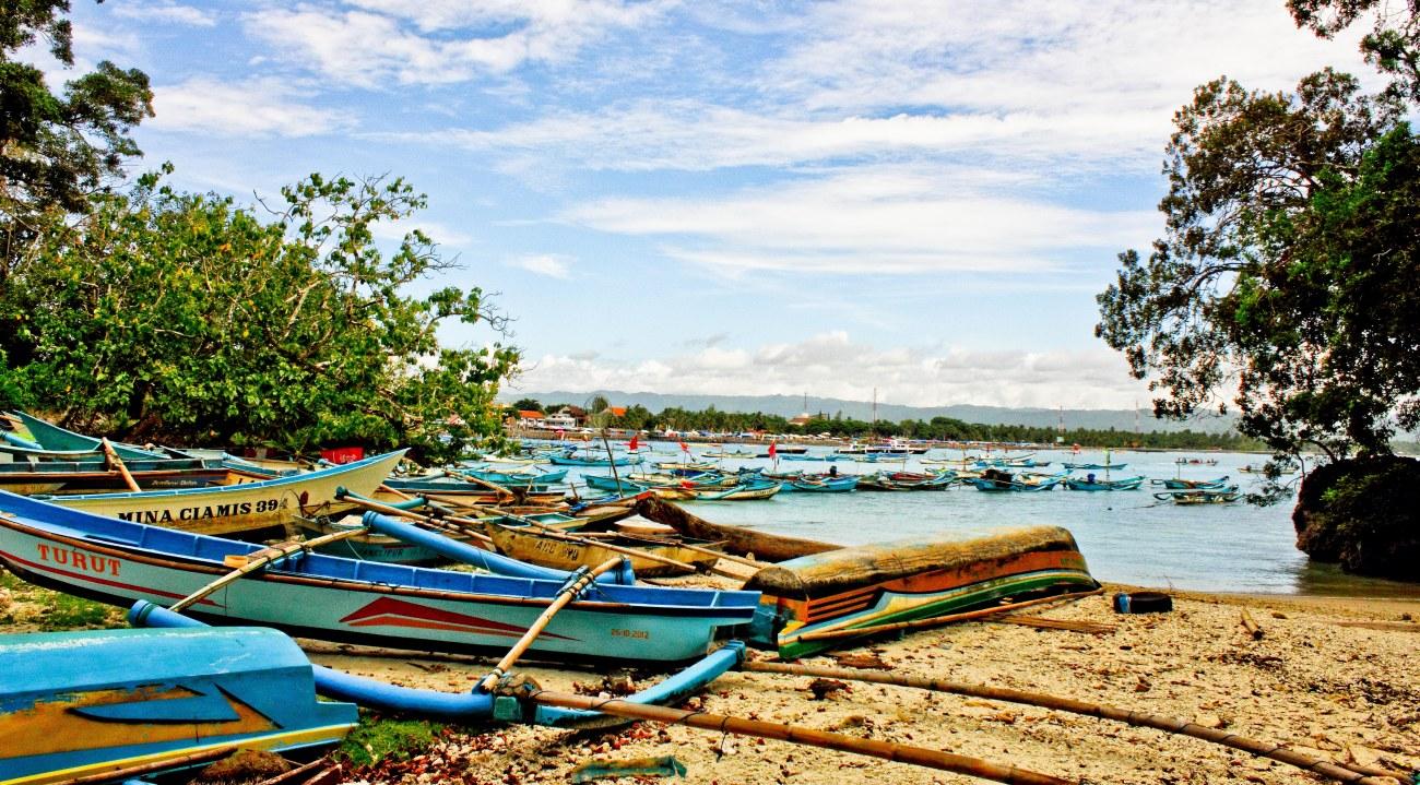 Berserakan perahu-perahu nelayan di atas Pantai Pasir Putih yang tidak terlalu luas.