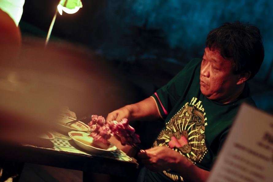 Pak Jono kayanya nih. Dia sedang menyiapkan sate yang akan dibakar.